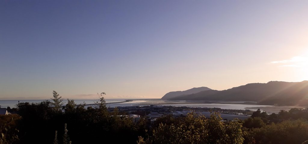 View of Nelson towards Wakapuaka with the boulder bank and estuary in the middle foreground. Sun rising in the east